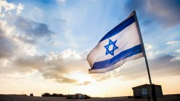 The flag of Israel set in front of a sun rise over the desert.