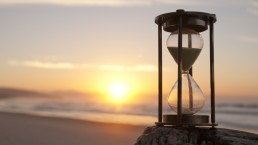 An hourglass sits on a rock on a beach as the sunsets over the ocean.