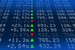 A digital stock exchange panel lists several stocks along with related metrics.