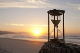 An hourglass sits on a rock on the beach in front of a golden sunset over the water.